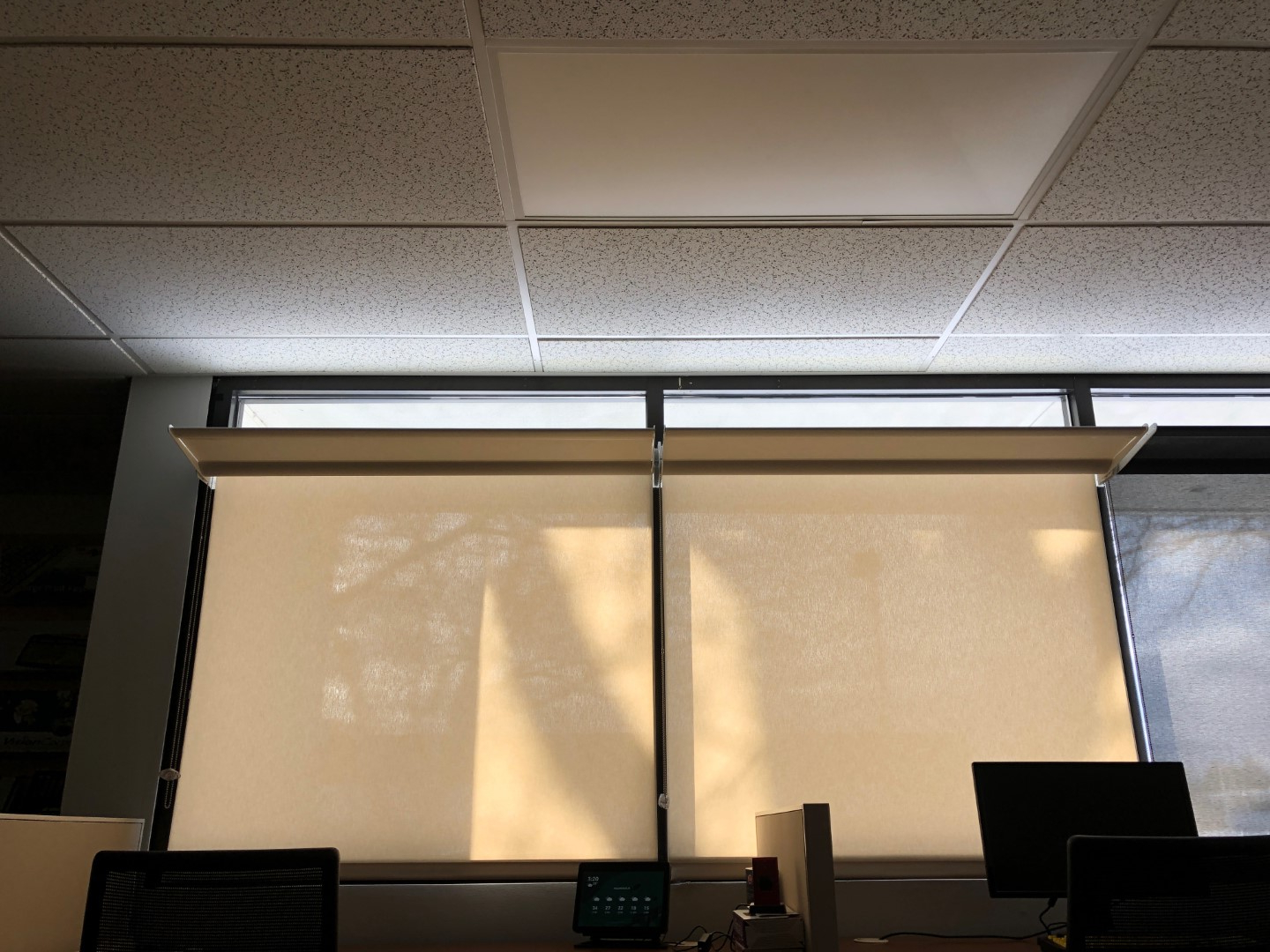 Office window  with shades drawn and lightshelf open. Daylight spreads across the ceiling.